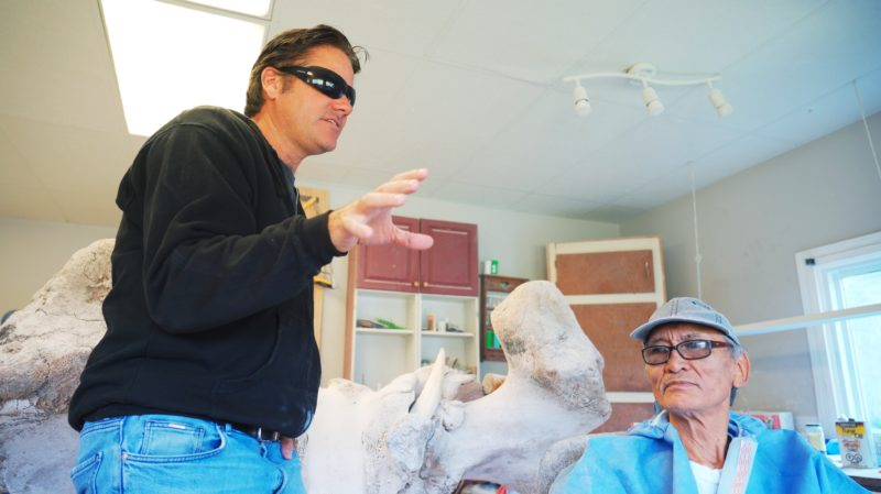 Man with sunglasses next to Inuit Artist